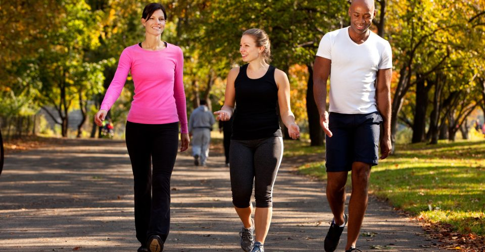 Two women and a man walking for fitness