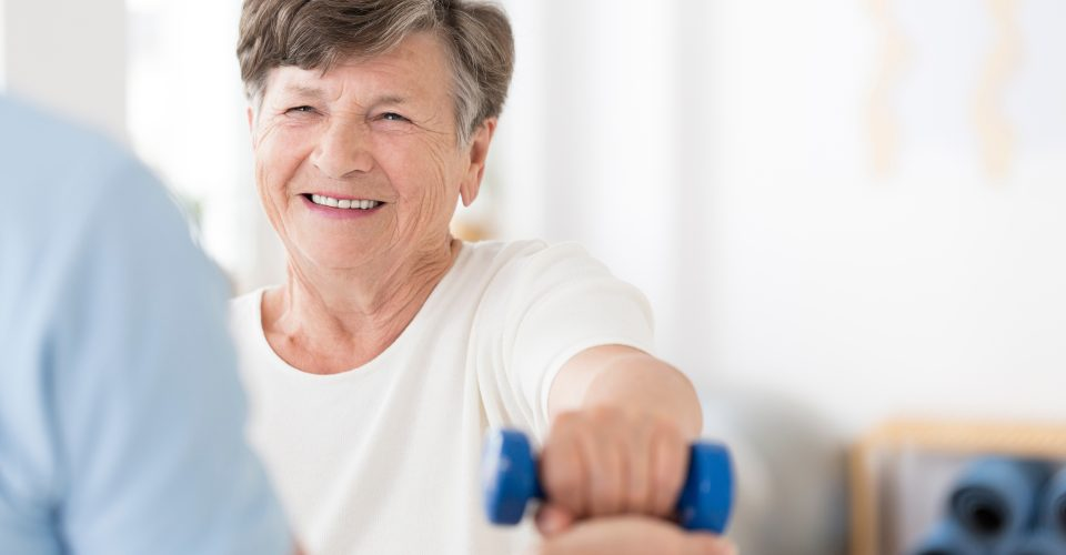 Older woman smiling while lifting small weight
