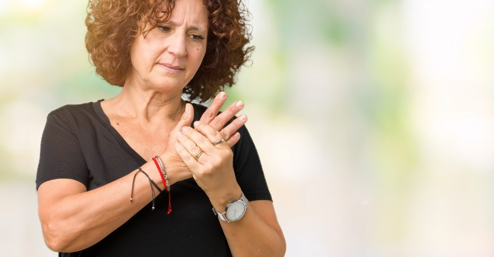 Middle aged woman holding arthritic hands