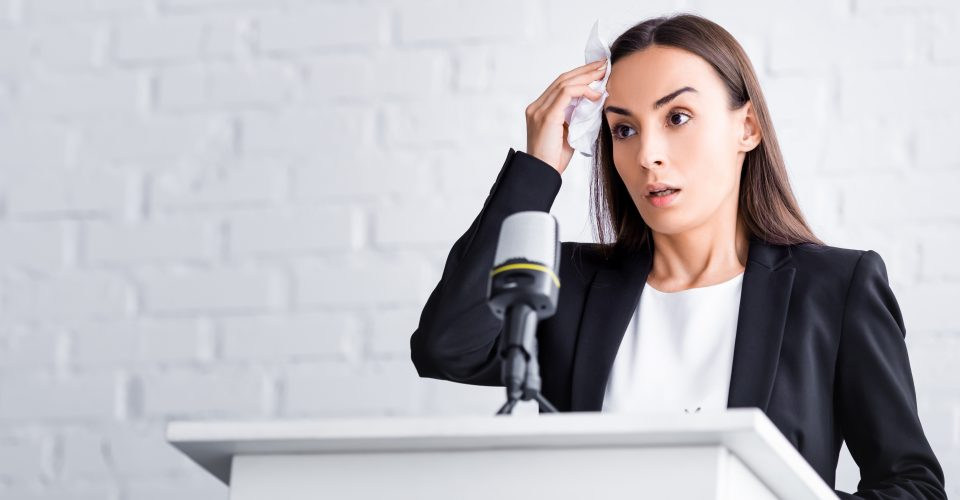 Woman standing at podium with a public speaking fear