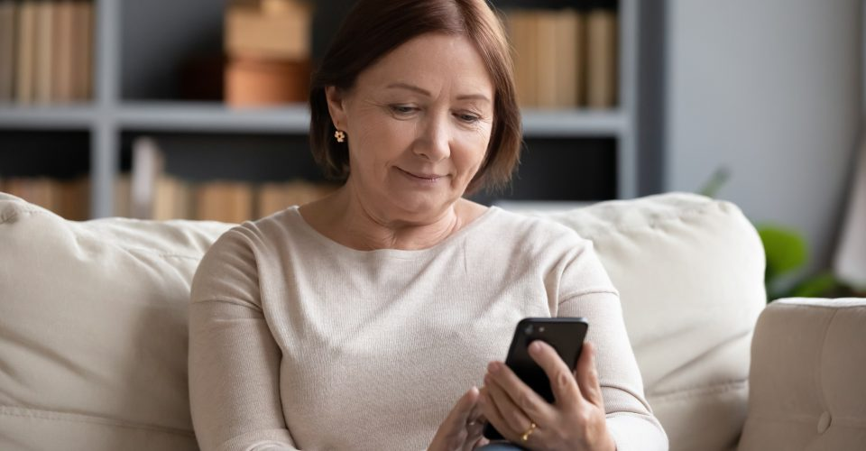 Woman sitting on couch looking at phone