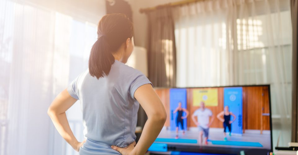 Woman exercising with a video on TV