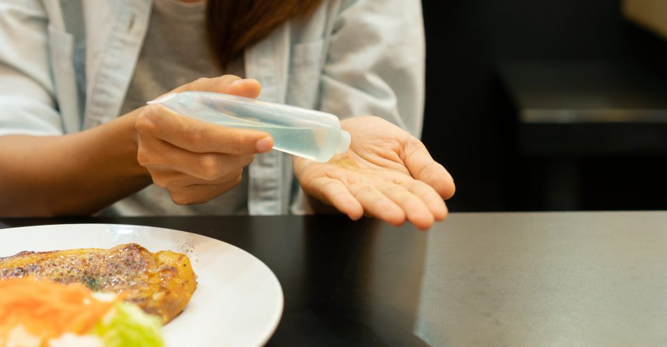 Woman putting hand sanitizer on hand before eating