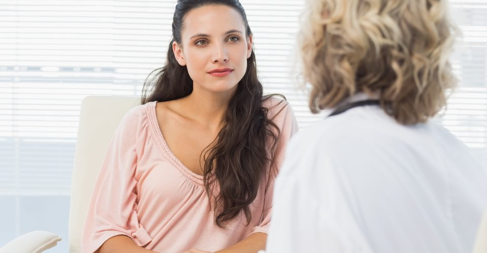 Woman sitting talking to doctor