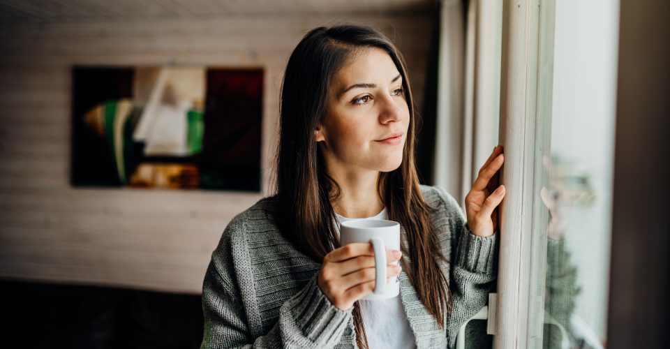 Woman holding a coffee mug looking out a window