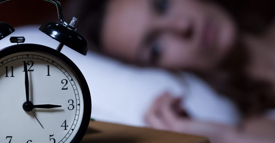 Woman laying in bed starting at alarm clock