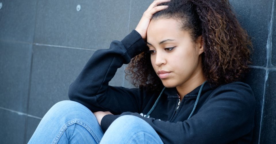 Teen sitting with hand on her head looking down