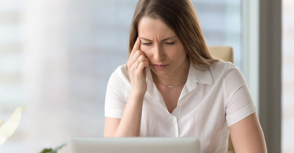 Woman experiencing confusion looking at a laptop