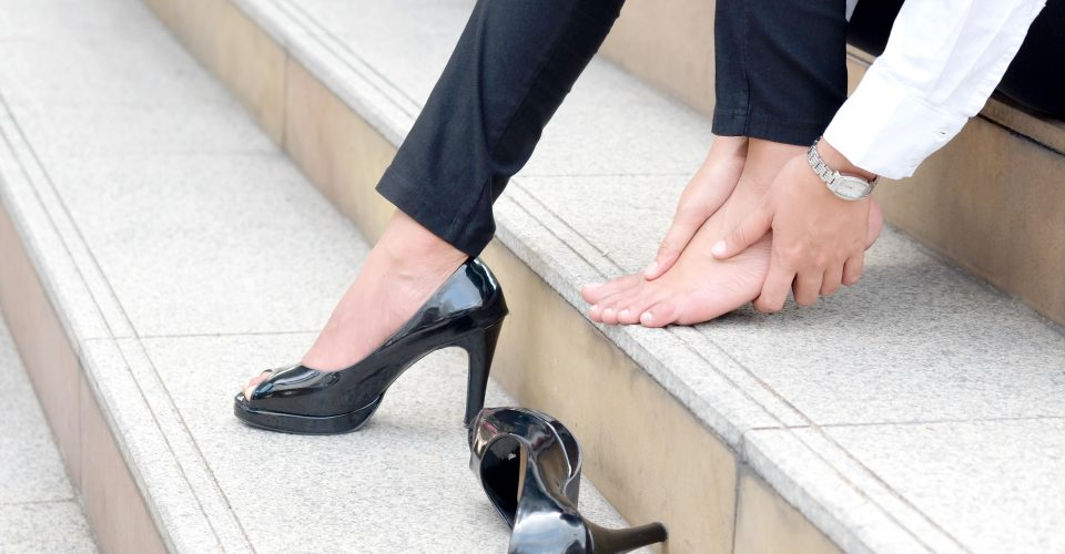Woman sitting on steps with Plantar Fasciitis